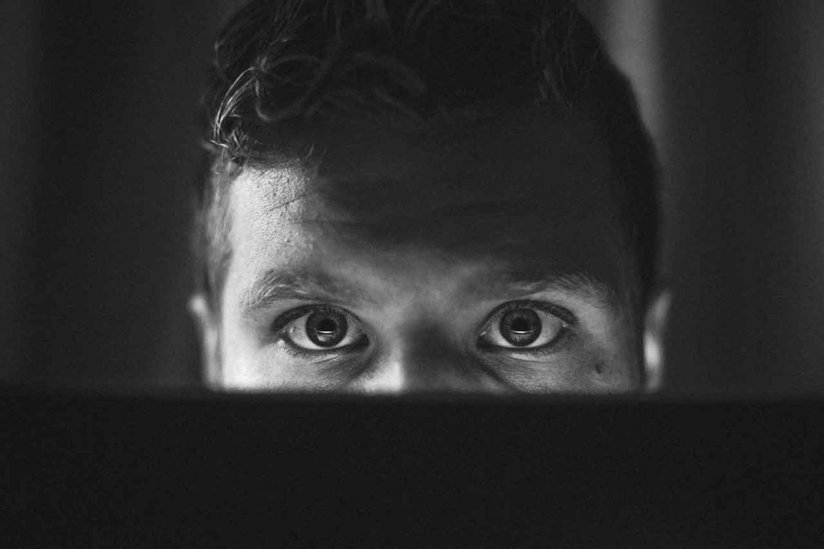Man tittar upp bakom en laptop