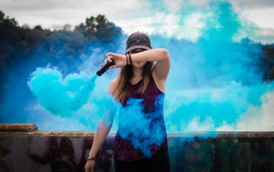 Kvinna sprider blå rök från en behållare